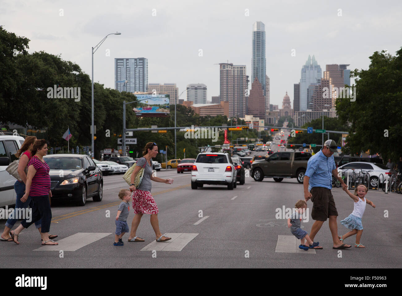 A family crosses the increasingly congested South Congress Avenue in Austin, Texas - Stock Image