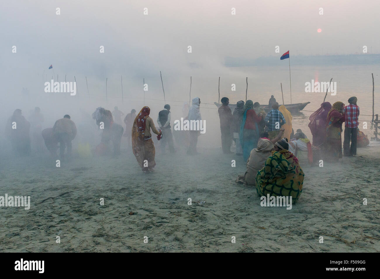 People taking bath in the fog early morning at the Sangam, the confluence of the rivers Ganges, Yamuna and Saraswati, Stock Photo