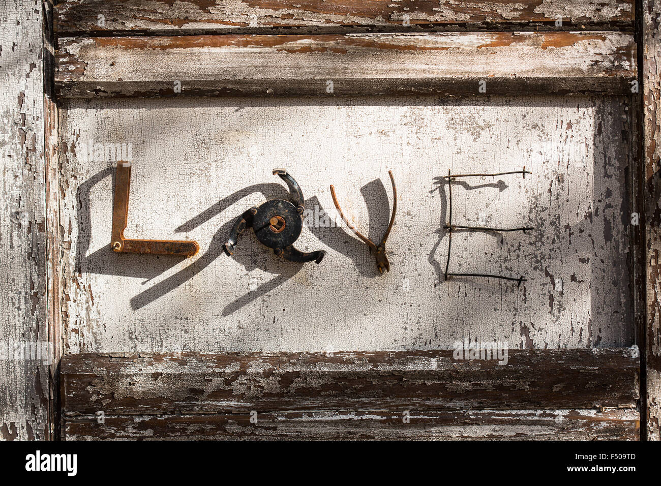 The word 'love' spelled out using metal parts on a wooden background - Stock Image