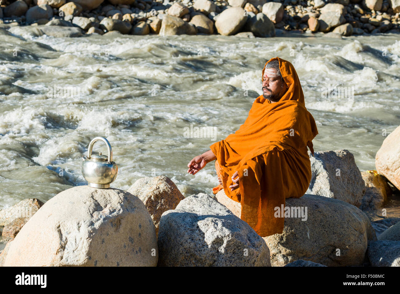 A Sadhu, holy man, is sitting on a rock and meditating at the banks of the river Ganges Stock Photo