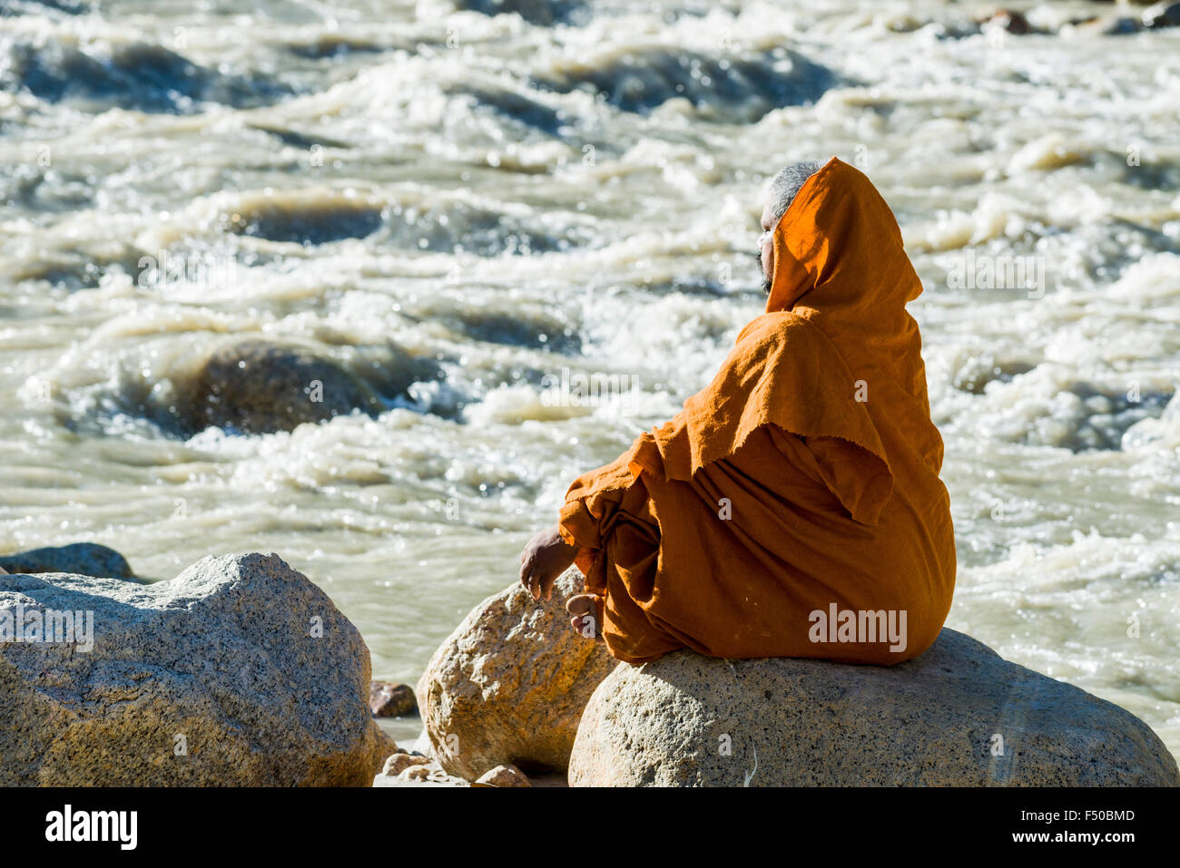 A Sadhu, holy man, is sitting on a rock and meditating at the banks of the river Ganges - Stock Image