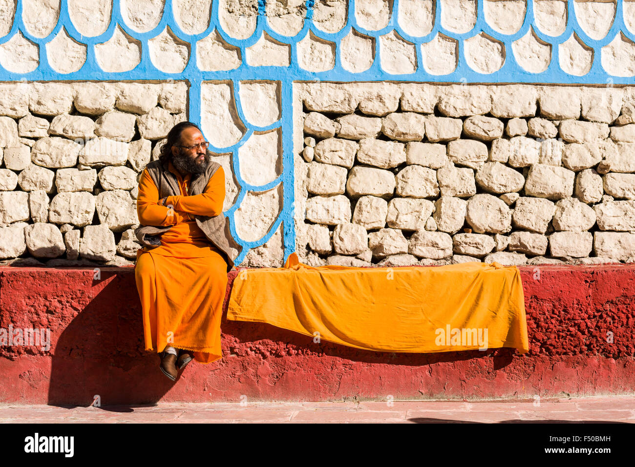 A Sadhu, holy man, is sitting on a wall at the banks of the river Ganges Stock Photo