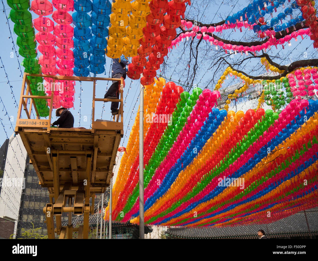 Workers hang colorful lanterns for Buddha's birthday at the Jogyesa temple in Seoul, South Korea - Stock Image