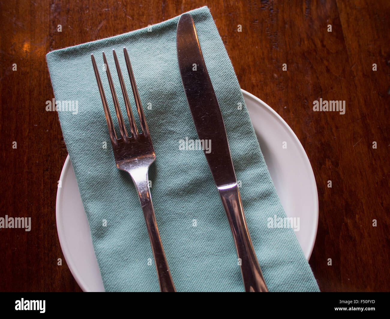 Silverware arranged on a napkin and plate - Stock Image