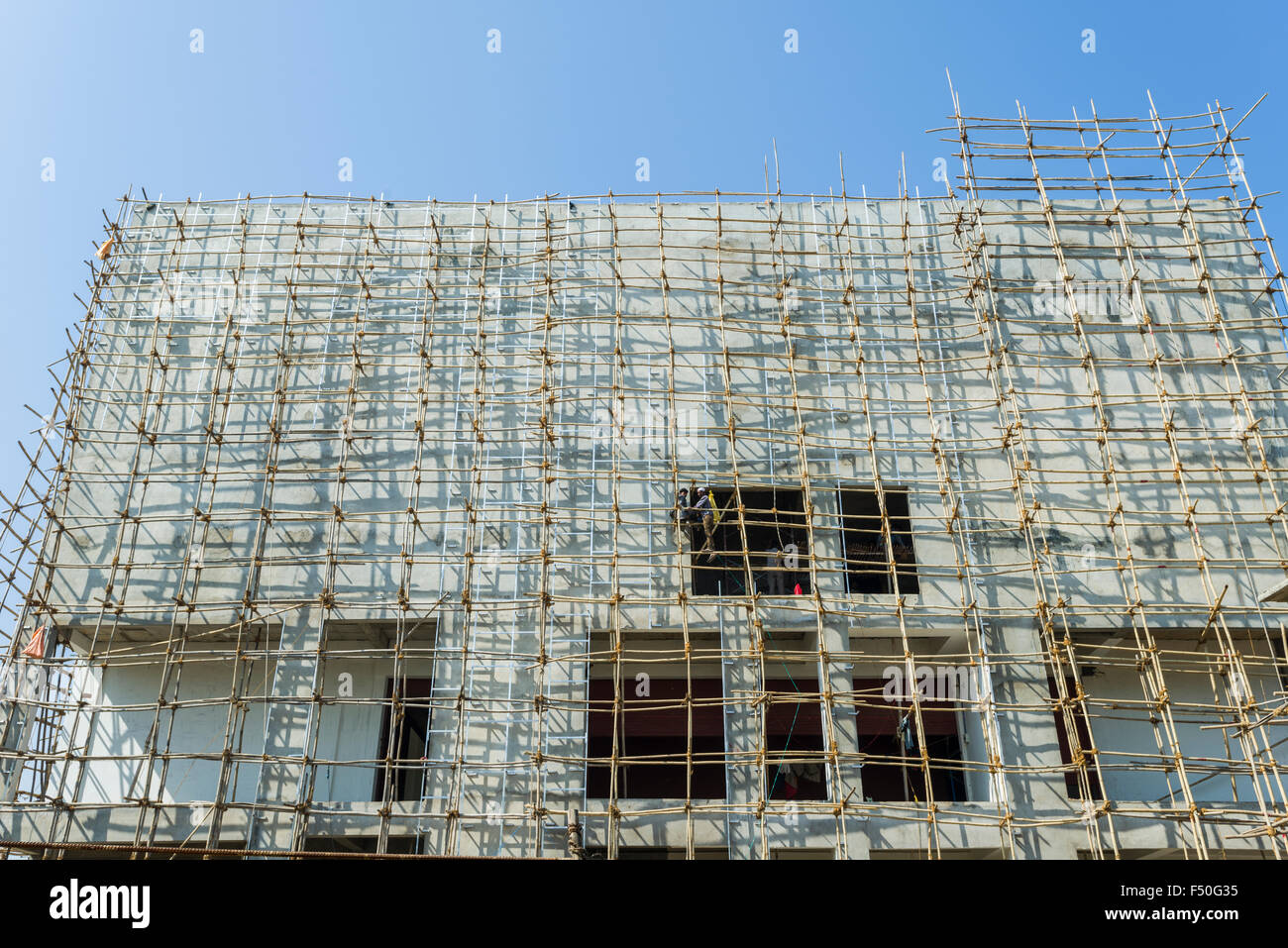 A construction site of a new concrete building with a bamboo scaffold attached - Stock Image