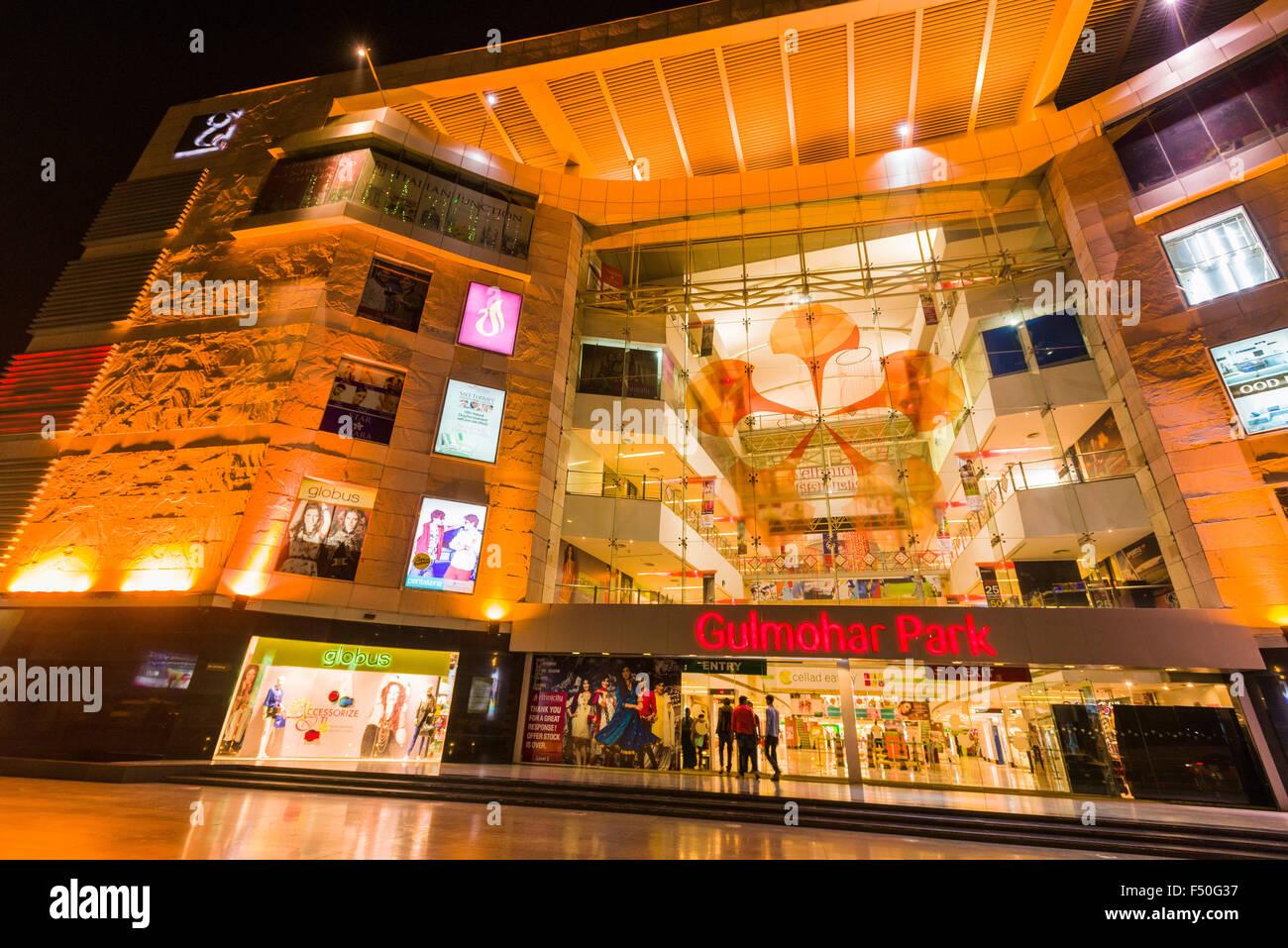 The entrance of the illuminated modern shopping mall Gulmohar Park at night - Stock Image