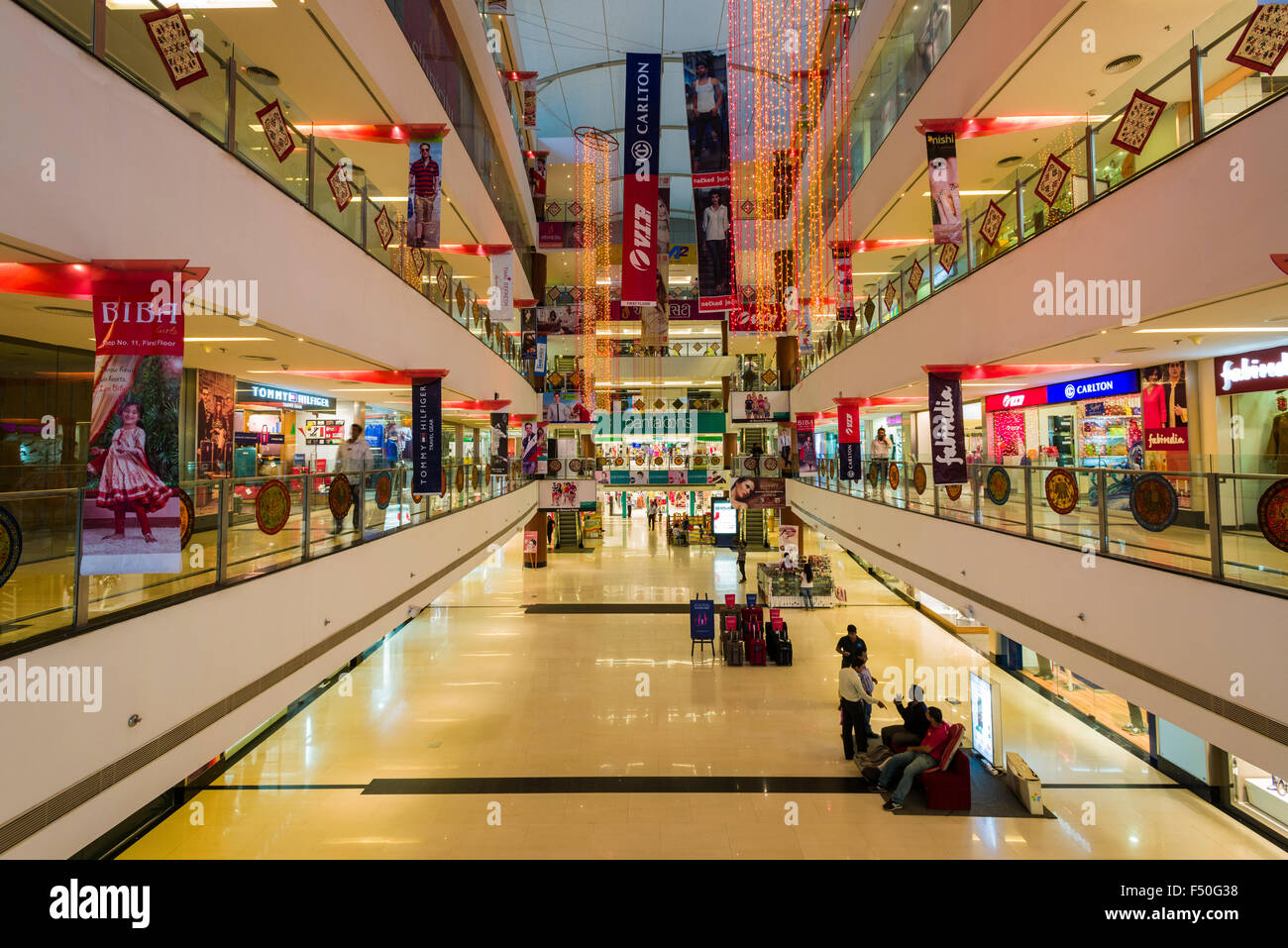 The main hall of the modern shopping mall Gulmohar Park with four floors and many shops - Stock Image