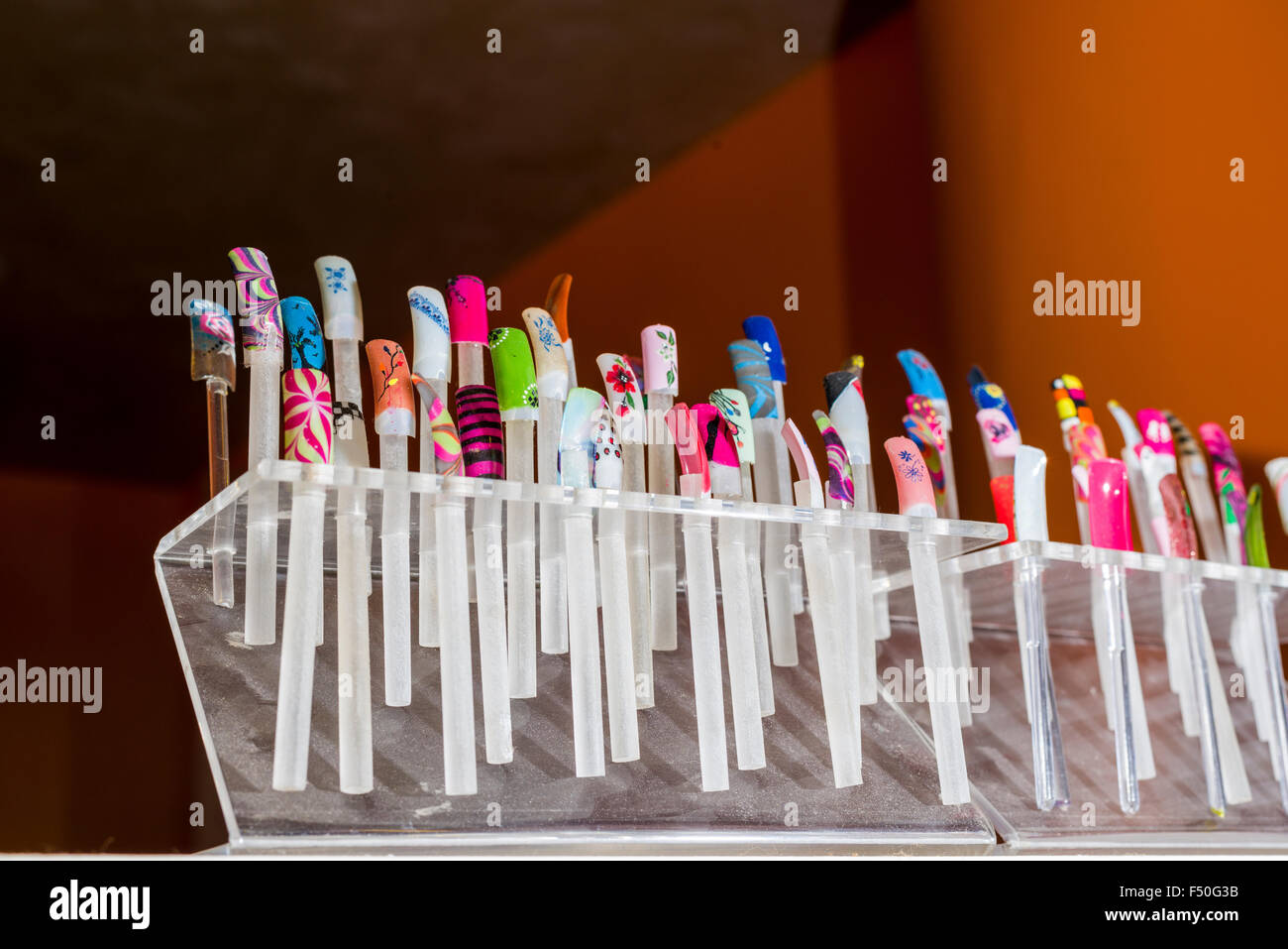 Nail extensions and nail disign are displayed for sale in one of the shops of the modern shopping mall Gulmohar - Stock Image
