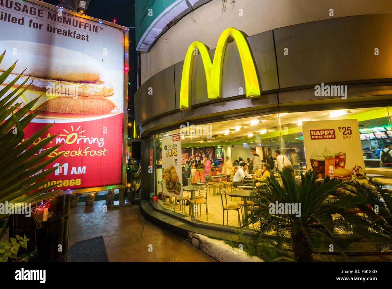 A western style McDonalds restaurant is frequented by modern Indians opposite the modern shopping mall Gulmohar - Stock Image