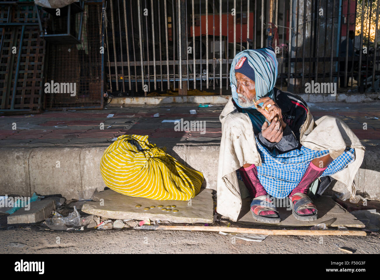 A homeless beggar is sitting on the pavement after spending the night sleeping on the concrete floor - Stock Image