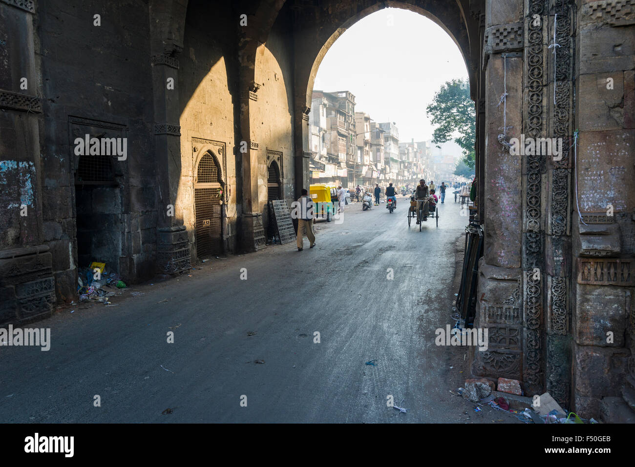 One of the historic City Gates of the old city with pedestrians and a cycle rikshaw - Stock Image