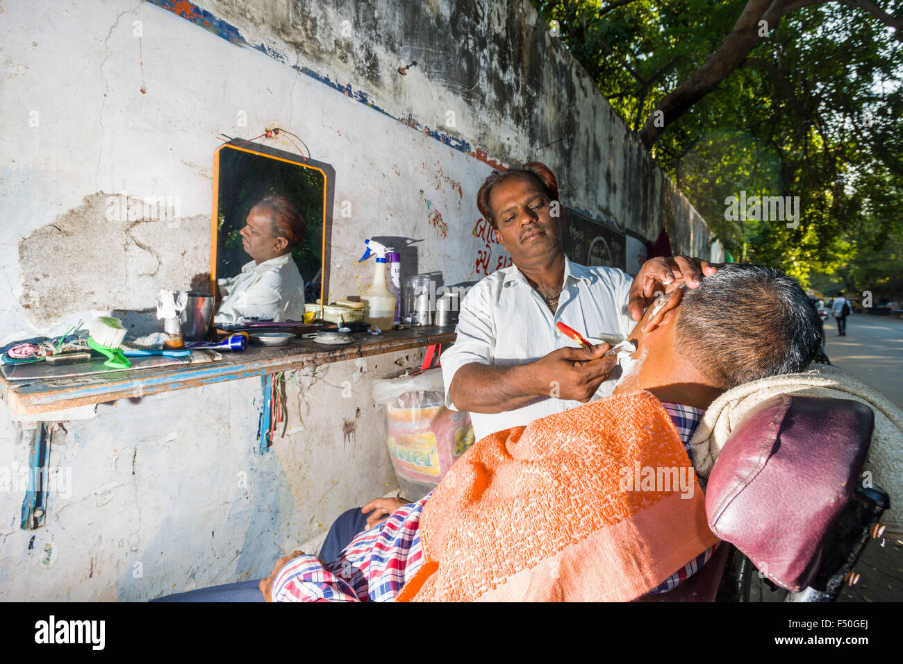 A barber is shaving a customer at his open air shop - Stock Image