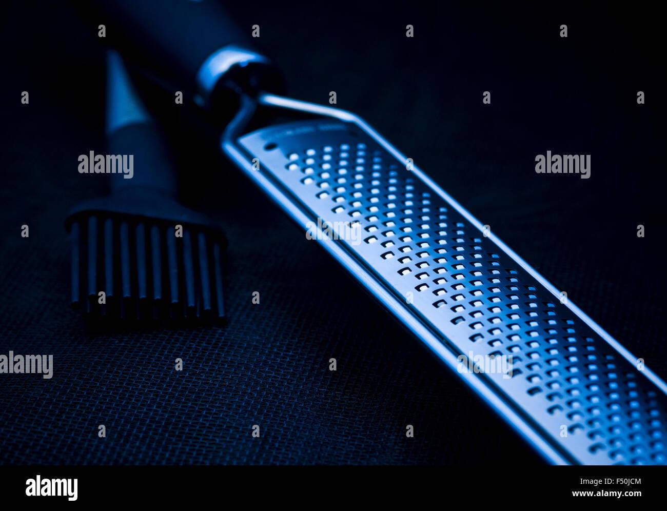 kitchen supplies;grater;brush;product shot;black mash;steel grater;blue light Stock Photo