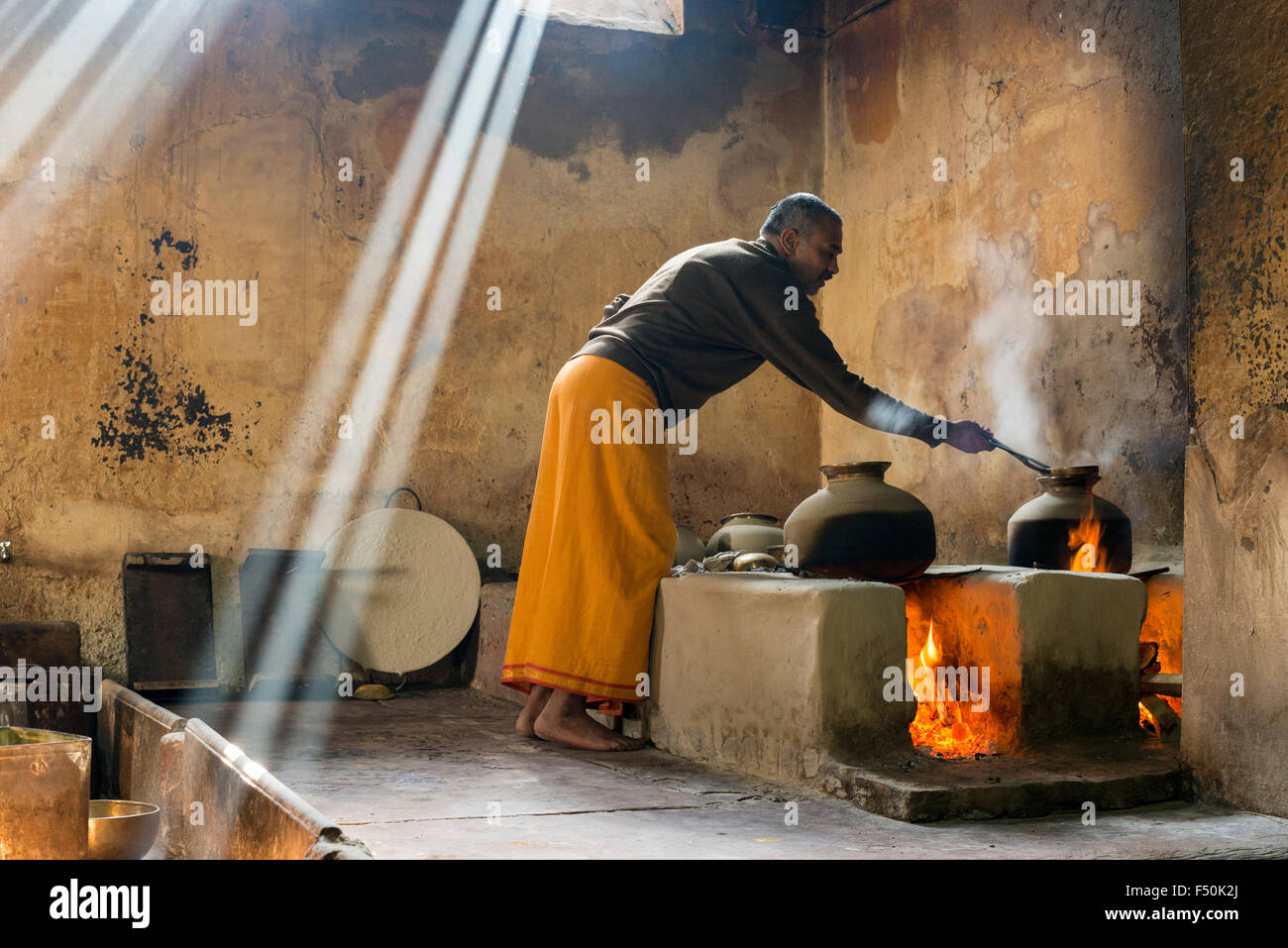 A priest, Brahmin, is cooking Prasad, holy food, for Holi festival at Radha Raman temple - Stock Image