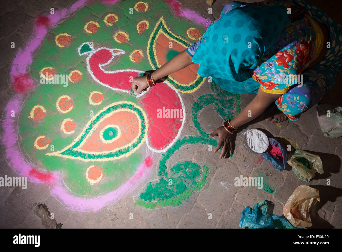 A woman is creating an artful Rangoli, made by colorpowder, at Holi festival on the street Stock Photo