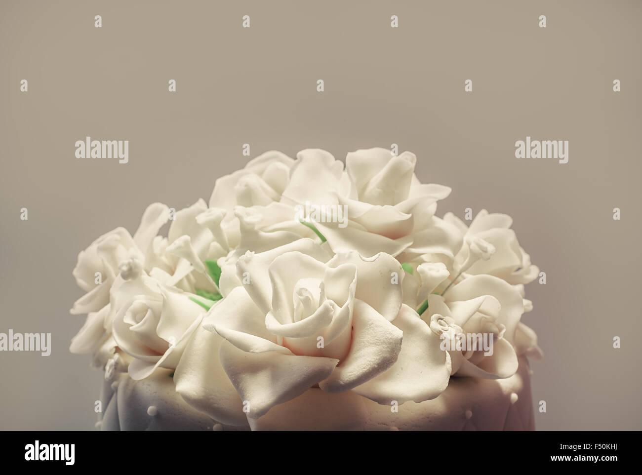 Details of a wedding cake, decoration with white fondant on white background. - Stock Image