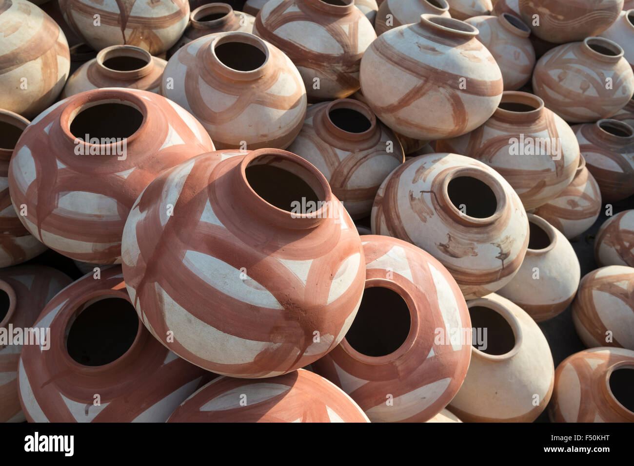 Many different terracotta and white colored clay flagons are for sale at a street shop Stock Photo