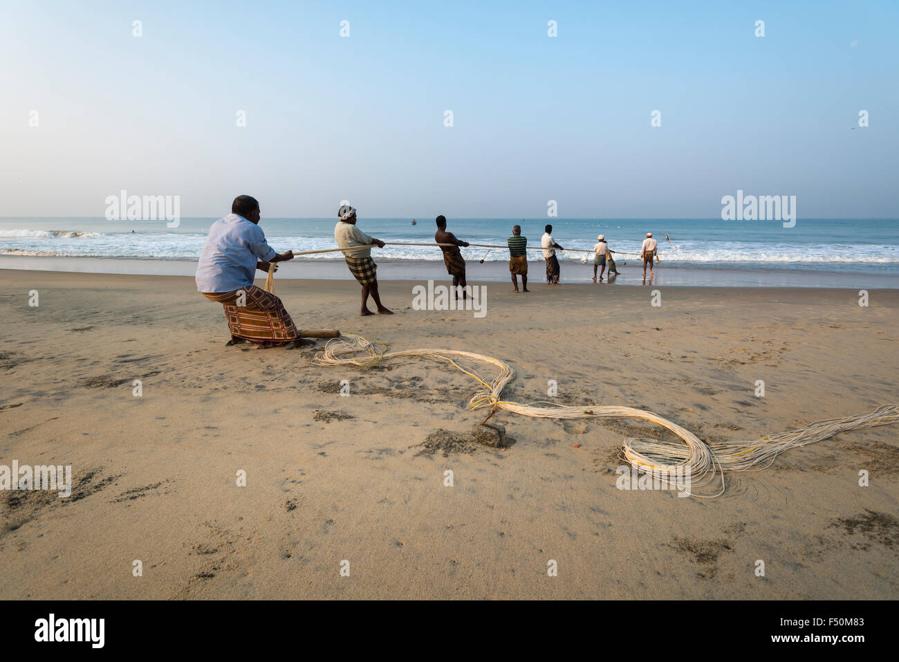 A group of fishermen is pulling out the fishing nets onto the beach - Stock Image