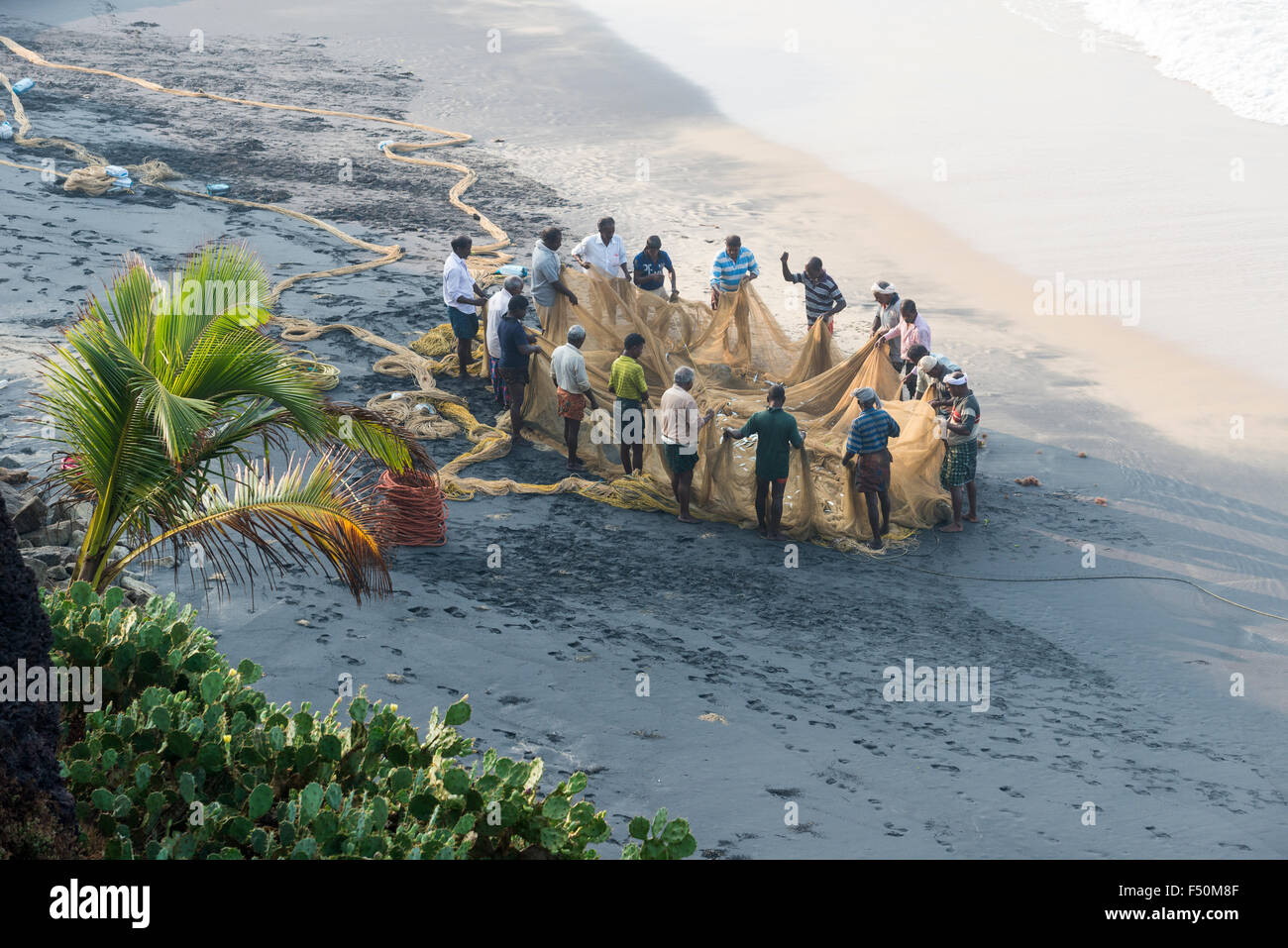 A group of fishermen is inspecting the fishing nets after pulling them out onto the beach - Stock Image