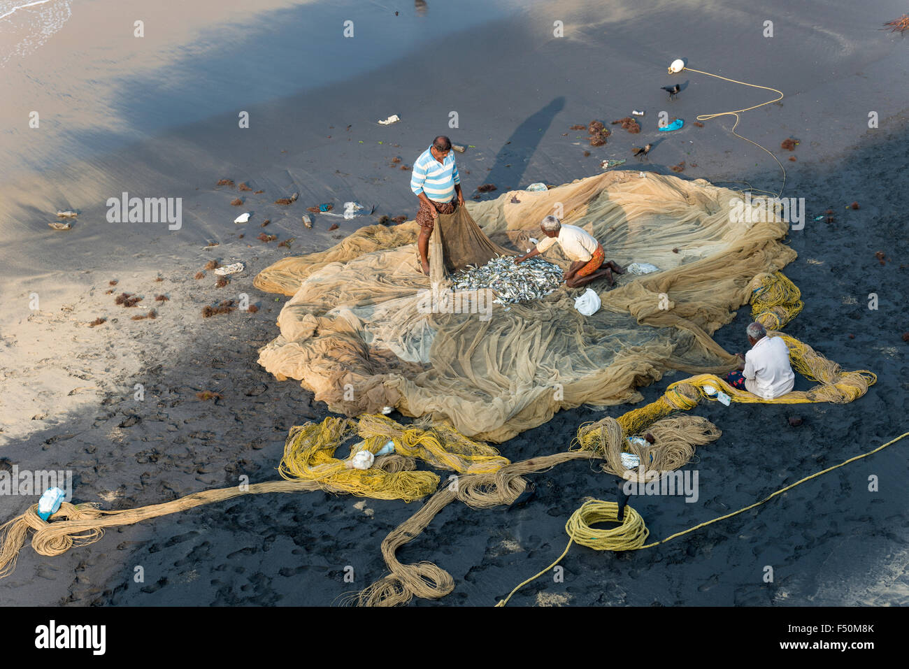 Two fishermen are inspecting the fishing nets after pulling them out onto the beach - Stock Image