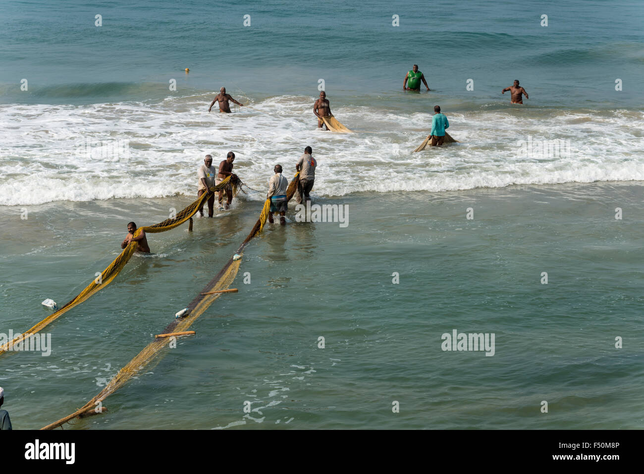 A group of fishermen, still standing in the water, is pulling out the fishing nets onto the beach - Stock Image