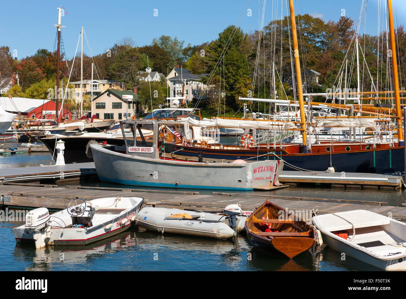 Dinghies line a dock in front of schooners and windjammers anchored in Camden harbor in Camden, Maine. - Stock Image