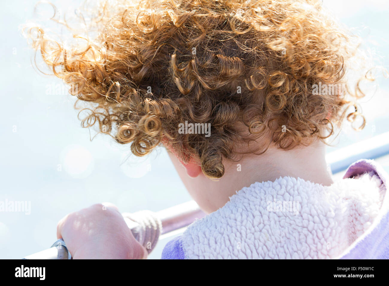 A curly haired young girl looking over a railing - Stock Image