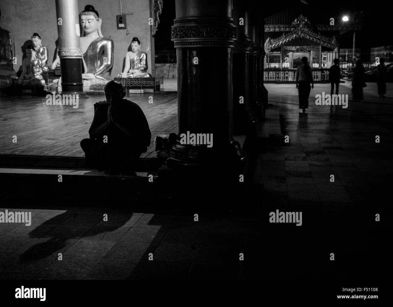 A monk praying in a temple at the Shwedagon  Pagoda in Yangon, Myanmar - Stock Image
