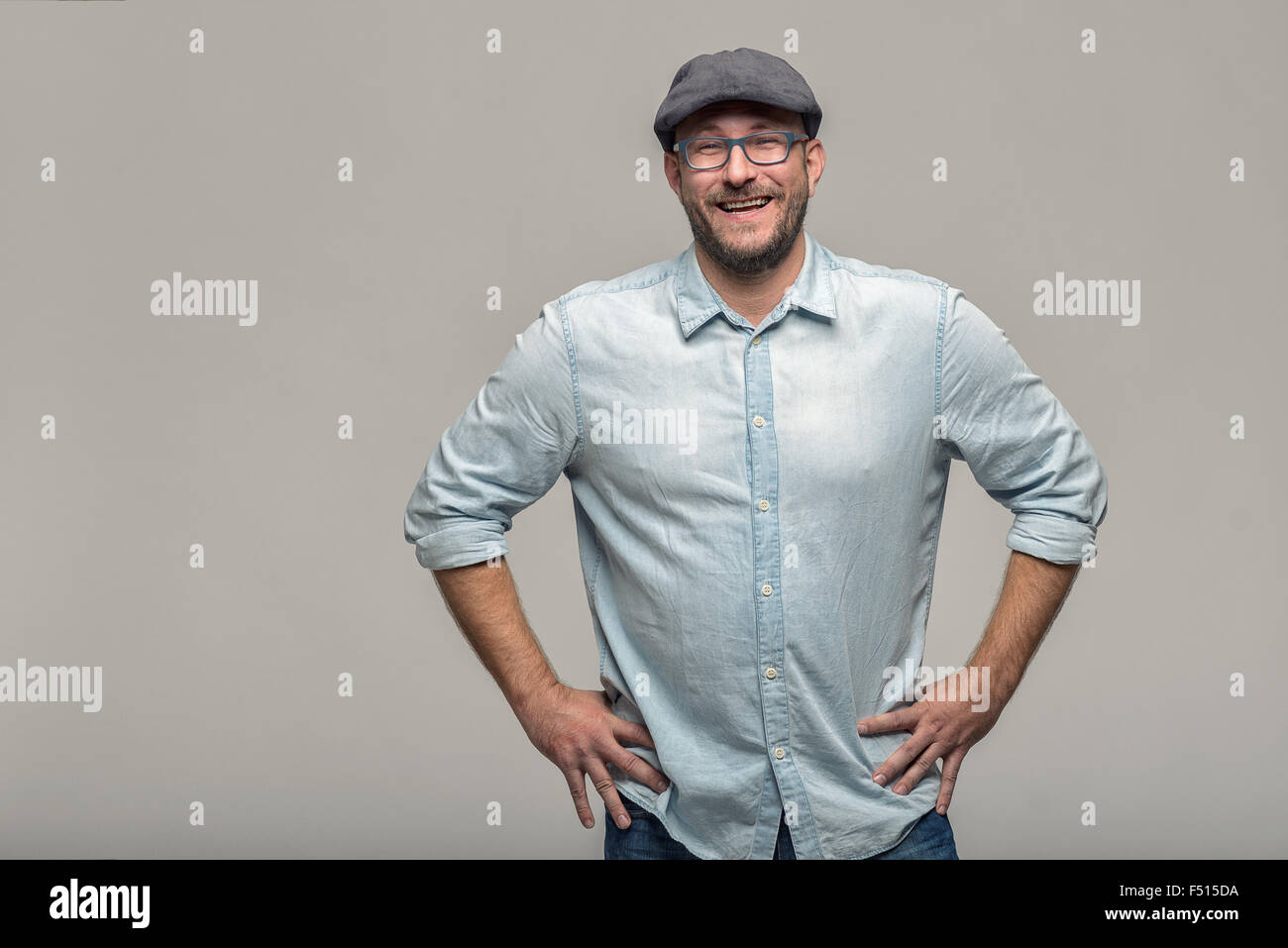 Friendly attractive man with glasses looking at the camera with a lovely warm smile, upper body over grey - Stock Image