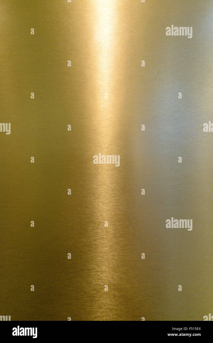 Detail of shiny polished metal surface golden (yellow) color with highlights - Stock Image