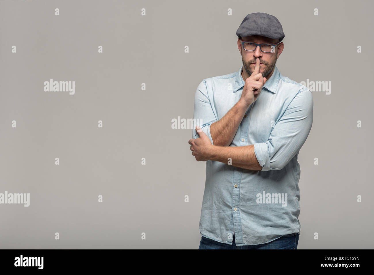 Middle-aged man wearing glasses and a cloth cap standing with a serious expression making a shushing gesture with - Stock Image