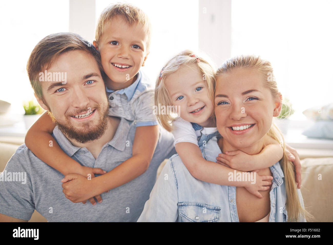 Happy kids embracing their cheerful parents - Stock Image