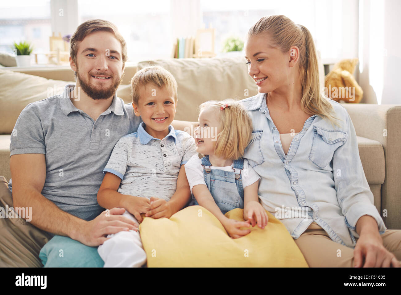 Happy family in casualwear sitting on sofa at home - Stock Image