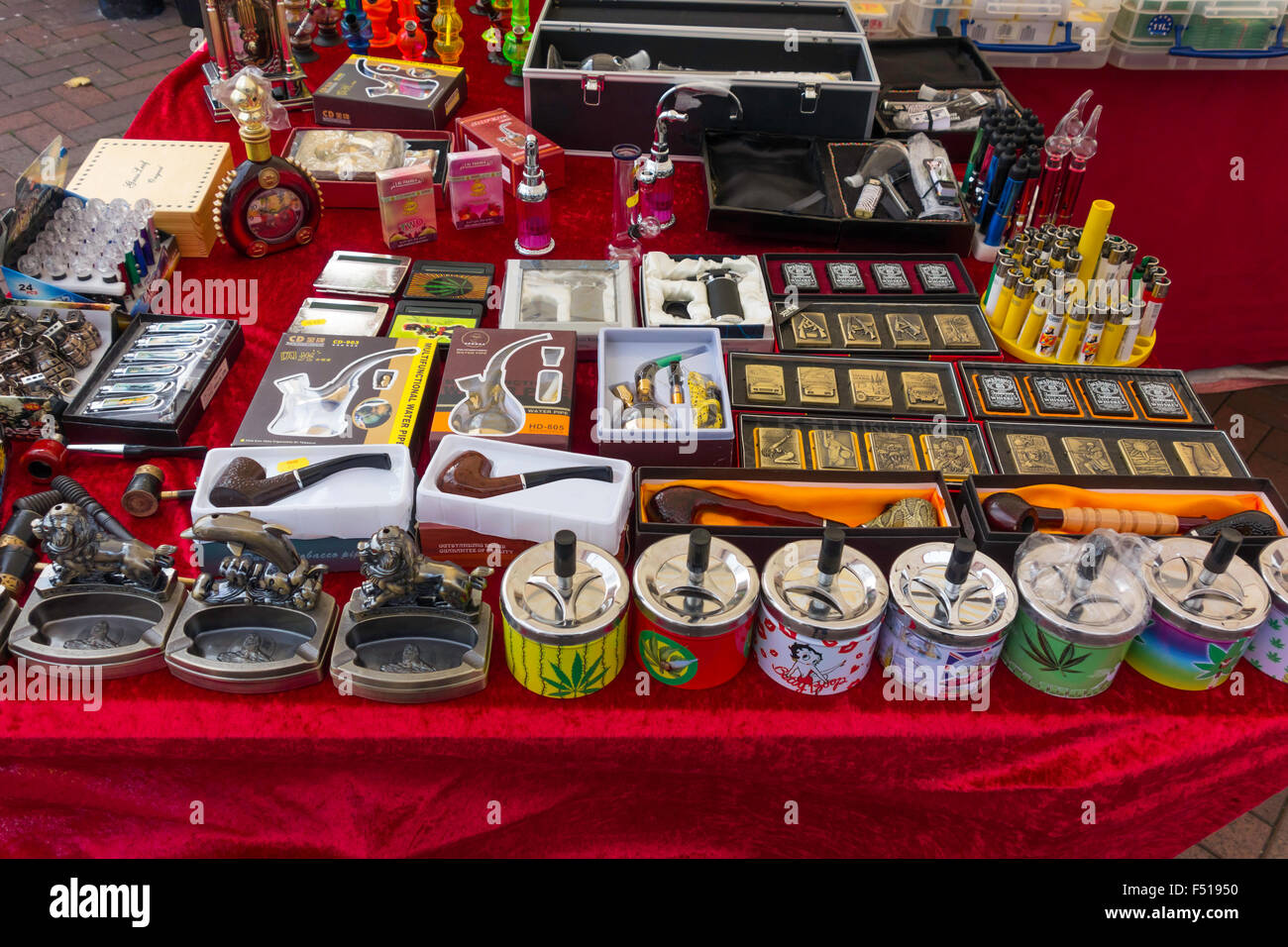 A display of smoking accessories pipes ashtrays lighters on a stall at a weekly small town English Market - Stock Image