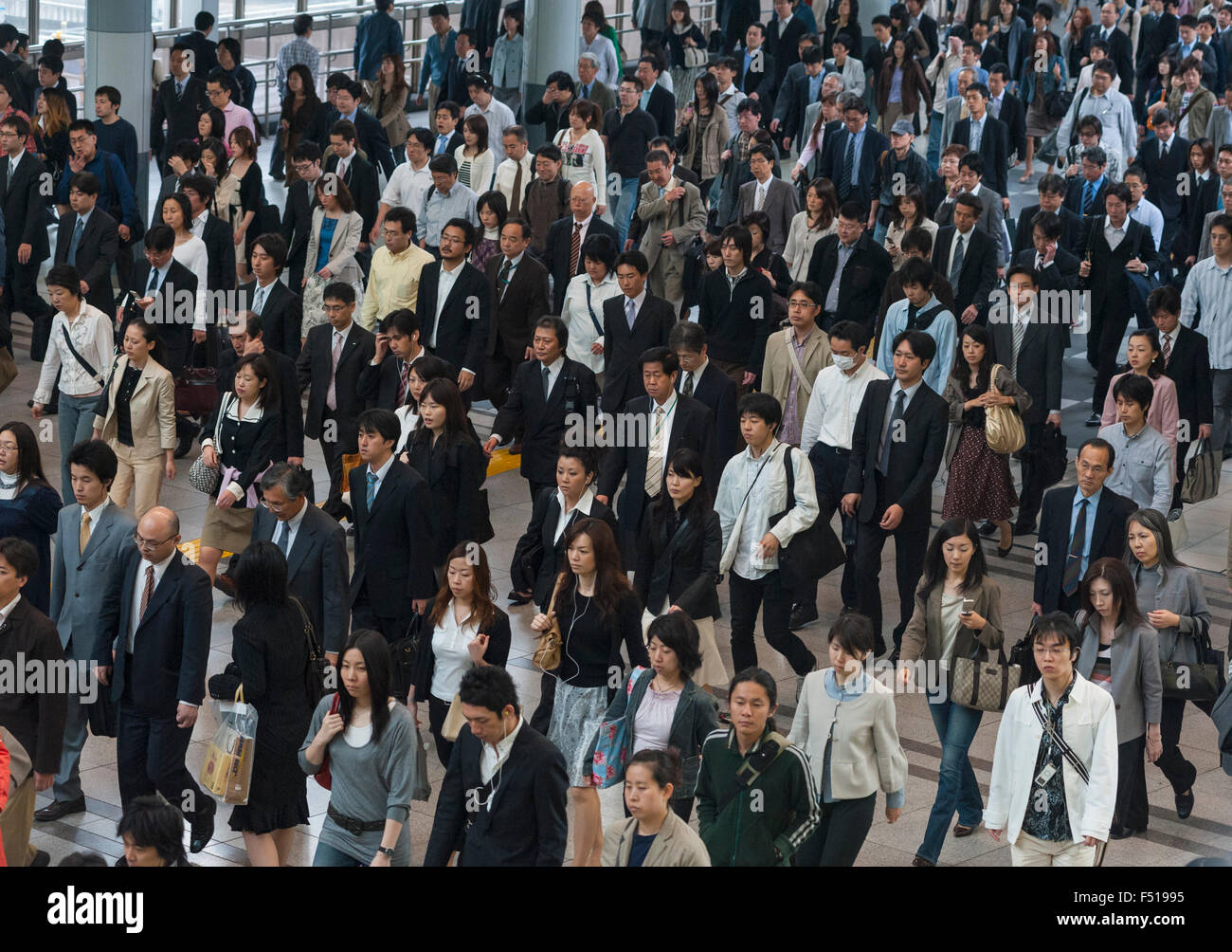 Many commuters walking through railway station during morning rush hour in central Tokyo Japan - Stock Image