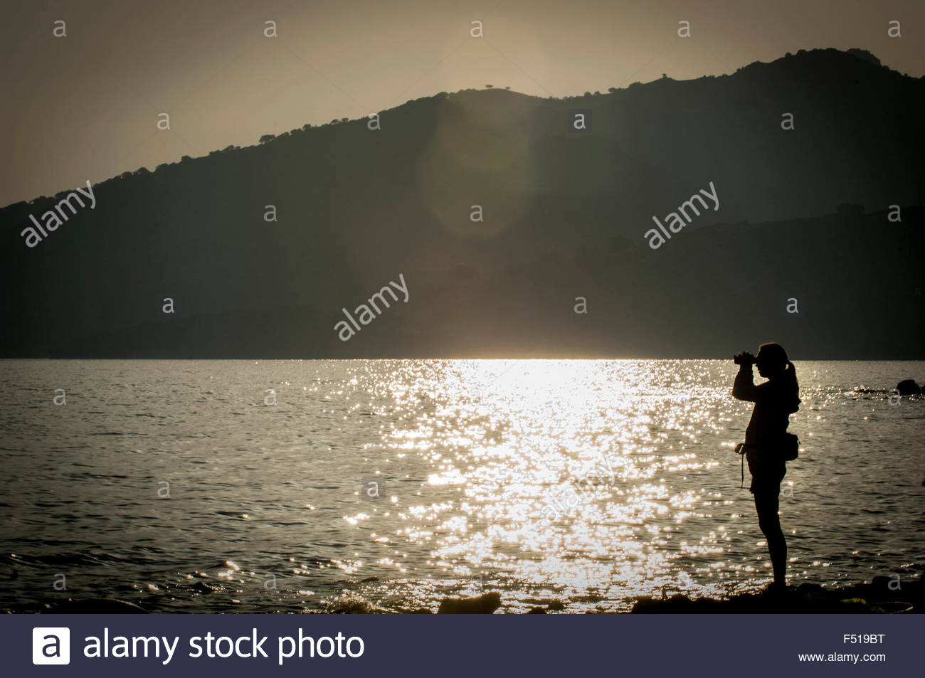 Hege Bjomebye is a voluntary aid worker from Norway and she uses her binoculars to spot the incoming boats to Lesbos - Stock Image
