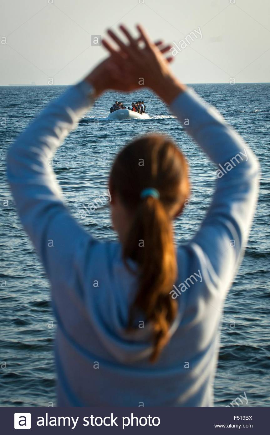 Hege Bjomebye, a voluntary aid worker from Norway waves to refugee boats arriving at 'Limantziki' beach - Stock Image