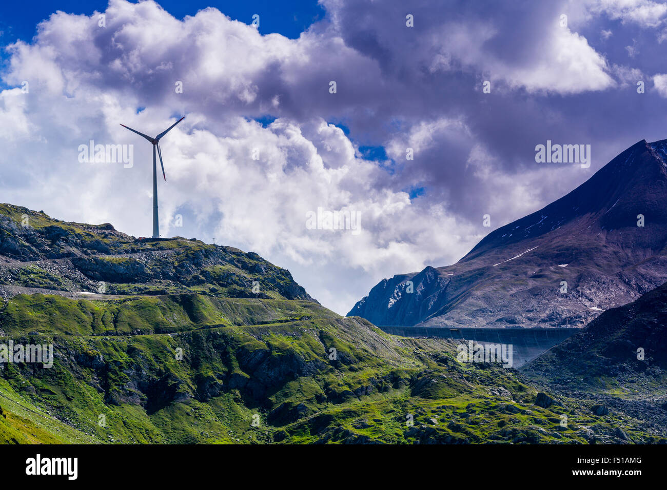 A wind powerplant is erected on mountains at high altitude near Nufenenpass, dark clouds at the sky - Stock Image