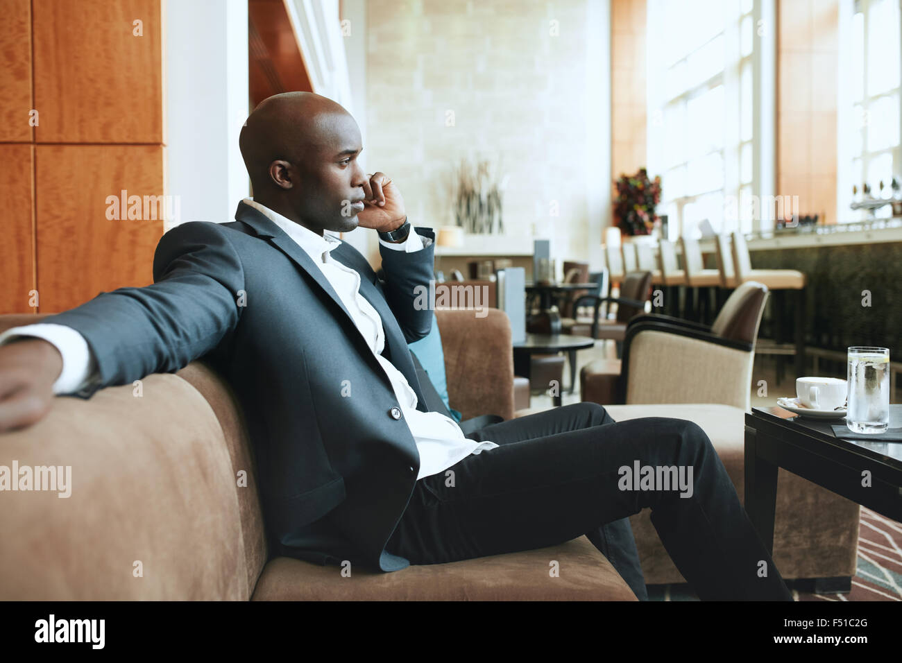Young businessman sitting relaxed on sofa at hotel lobby making a phone call, waiting for someone. - Stock Image
