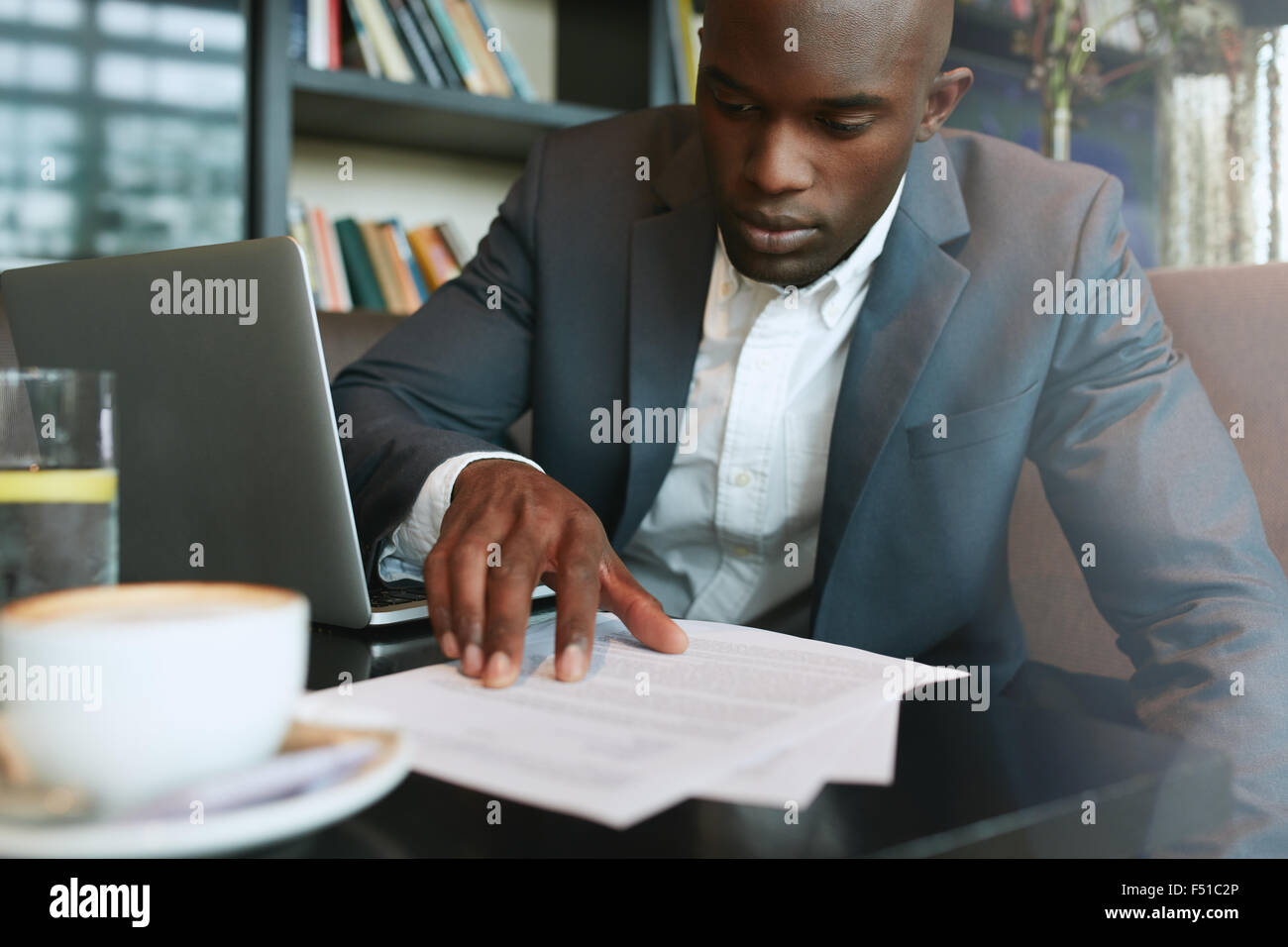 Businessman in a coffee shop reading a contract document. African business executive sitting at cafe working. - Stock Image