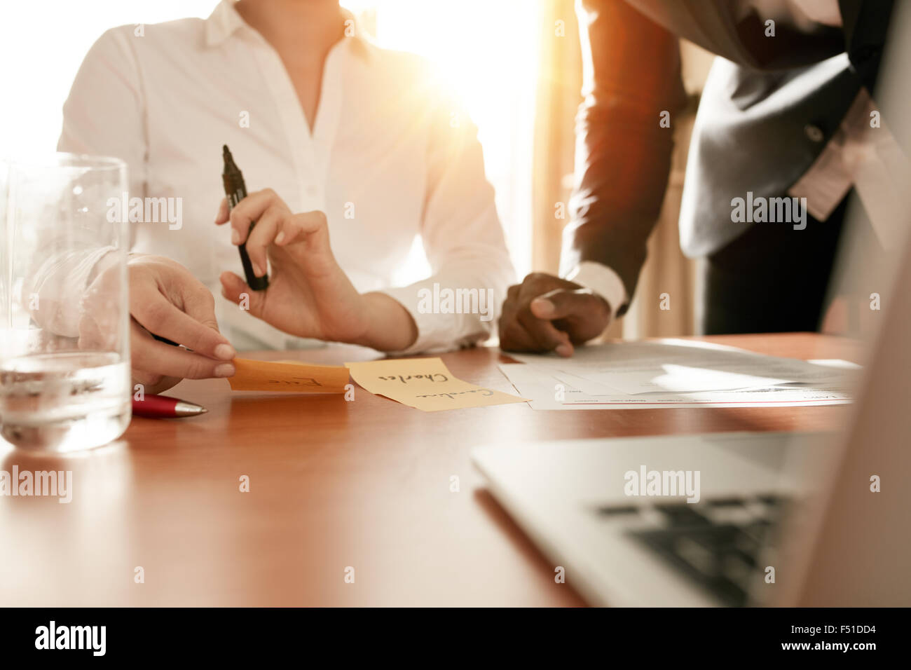 Cropped shot of two businesspeople discussing names written on sticky notes. Business executives doing manpower Stock Photo