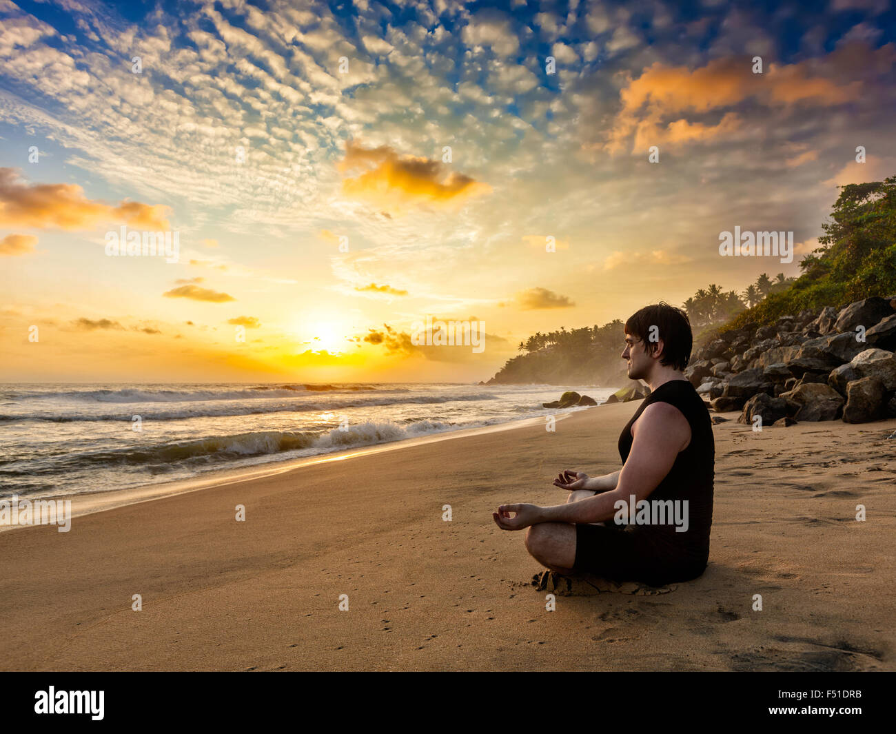 Young fit man do yoga meditation on tropical beach - Stock Image