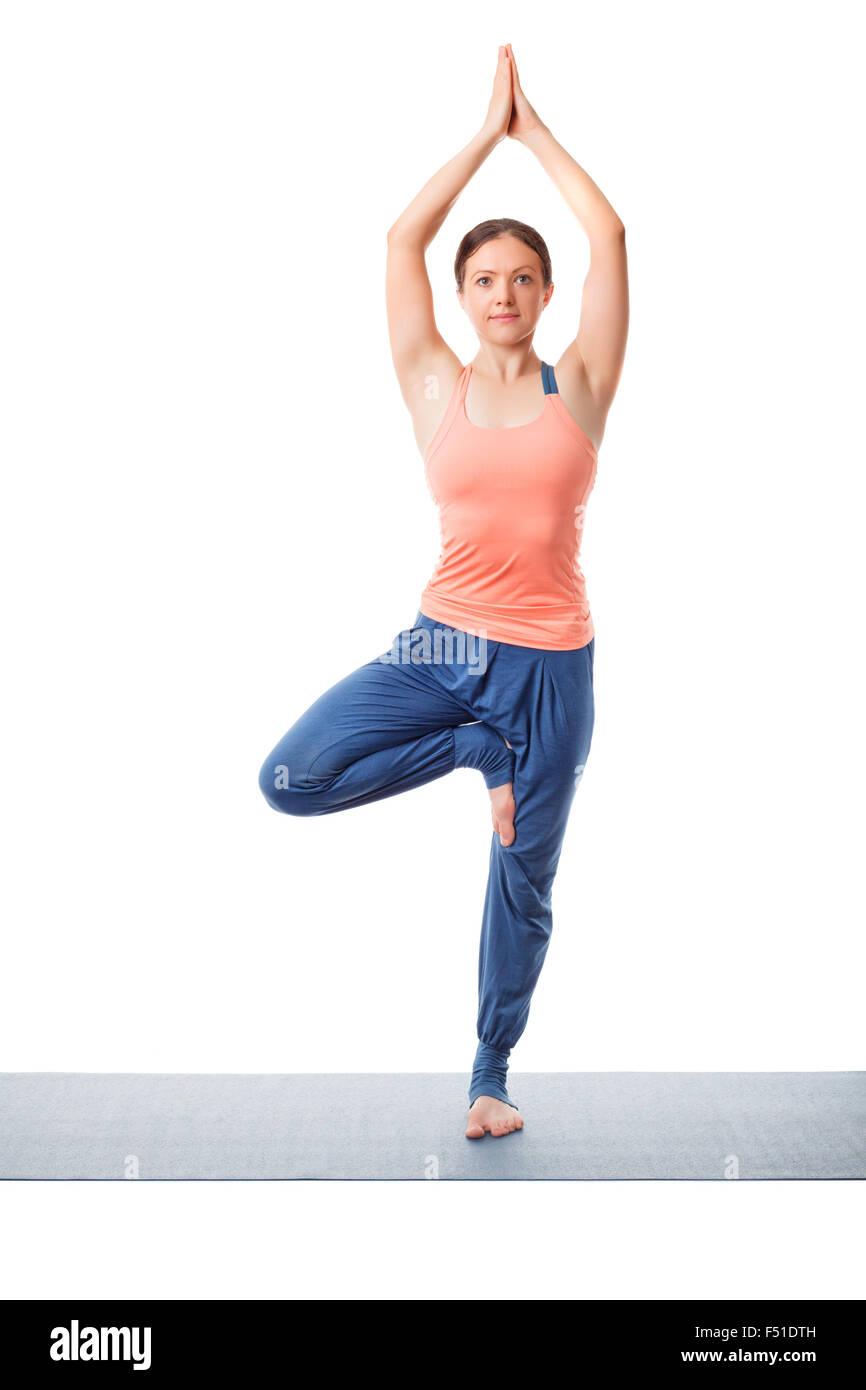 Woman practices yoga asana Vrikshasana tree po - Stock Image
