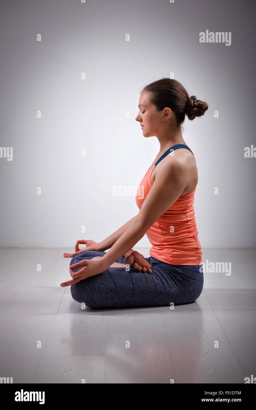 Woman meditate in yoga asana Padmasana Lotus pose - Stock Image