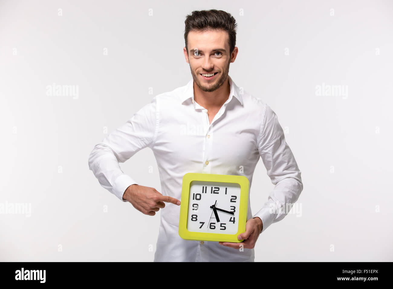 Portrait of a smiling businessman in shirt pointing finger on wall clock isolated on a white background - Stock Image