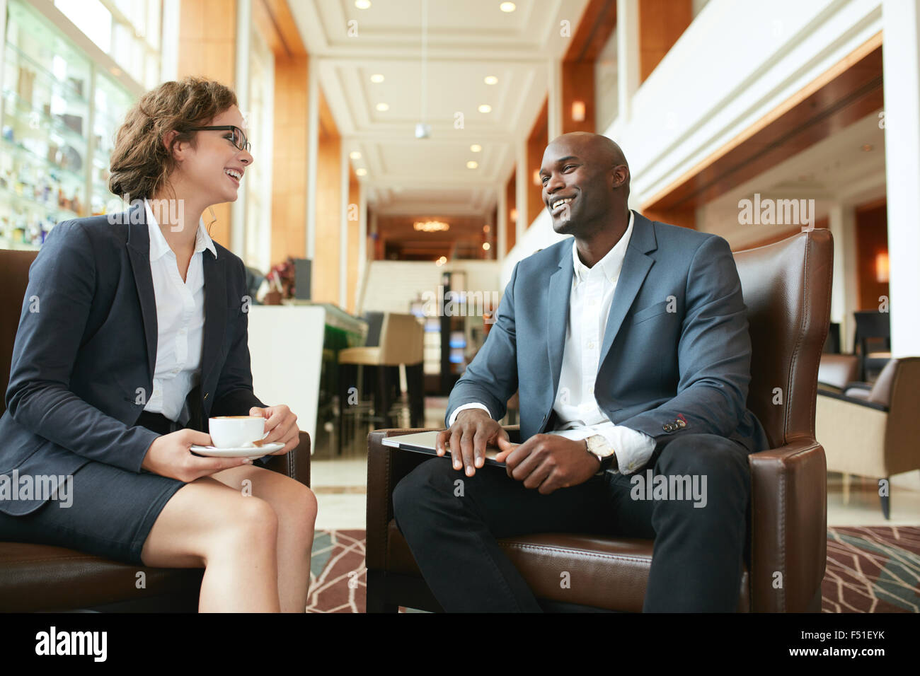 Portrait of happy young businesswoman in meeting with business partner at hotel lobby. Business people having a - Stock Image