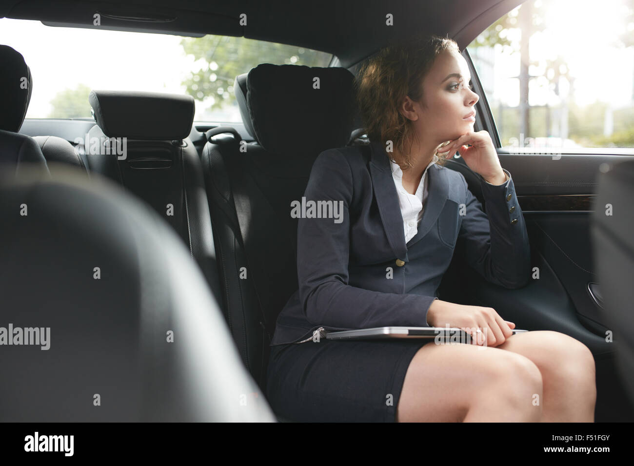 Young businesswoman traveling to work in the luxury car on the back seat looking outside the window. - Stock Image