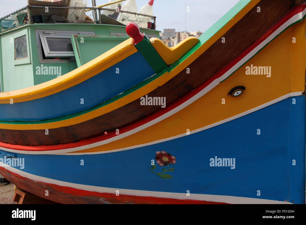 A traditional Maltese fishing boat, the Luzzu hauled up and being repainted on the harbour side - Stock Image
