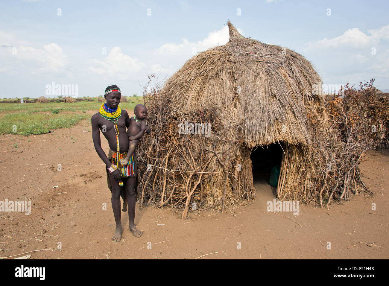 Young Nyangatom woman with baby in arms, stands next to her thatch hut. Omo Valley, Ethiopia Stock Photo