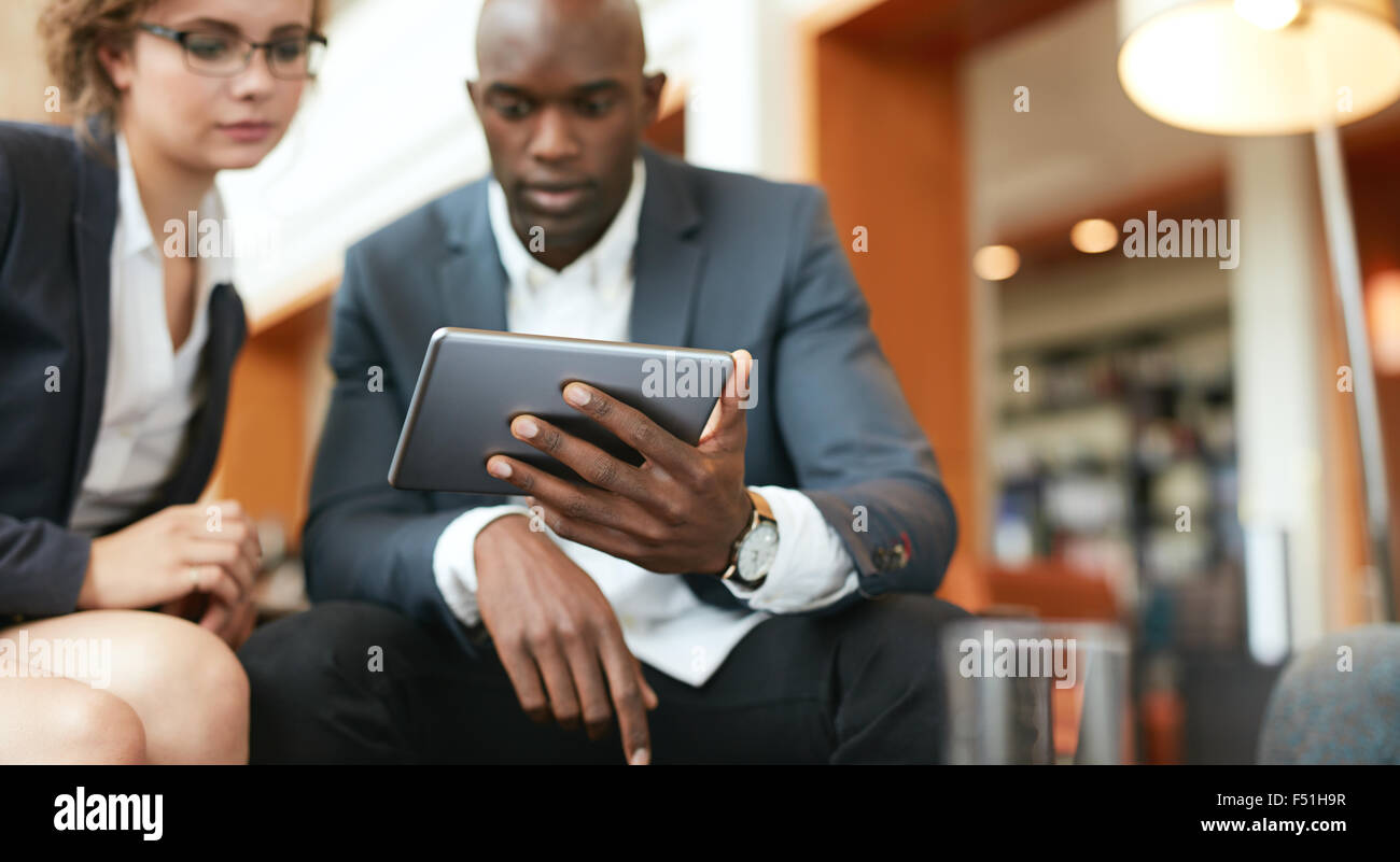 Shot of businesspeople sitting together looking at digital tablet. Focus on digital tablet in man's hand. - Stock Image